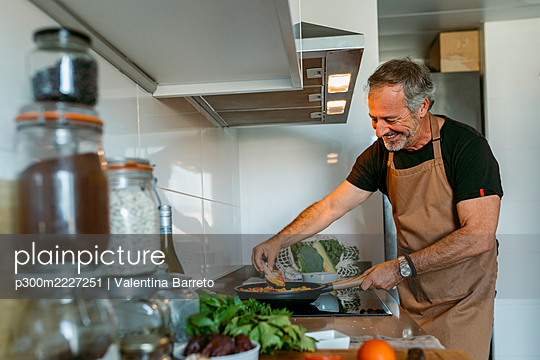 Happy mature man preparing pasta while standing in kitchen at home - p300m2227251 by Valentina Barreto