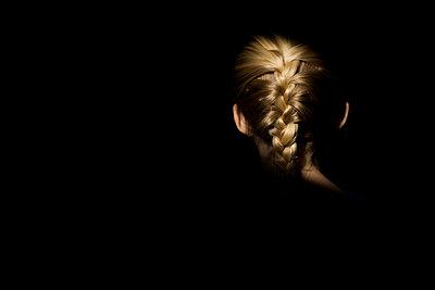 Blonde girl braid in light with dark background - p1166m2200931 by Cavan Images