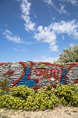 Old stone wall covered with graffiti - p1682m2264033 by Régine Heintz