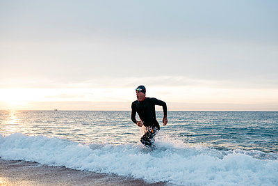 Male swimmer leaving water after swimming in sea at sunset - p300m2243022 by Josep Rovirosa