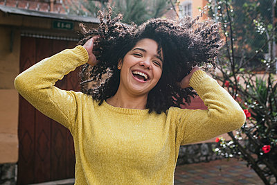Cheerful woman playing with curly black hair at back yard - p300m2265563 by MORNINGVIEW AGENCY