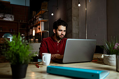 Mid adult male freelancer with coffee cup working on laptop in cafe - p300m2276358 by Rafa Cortés