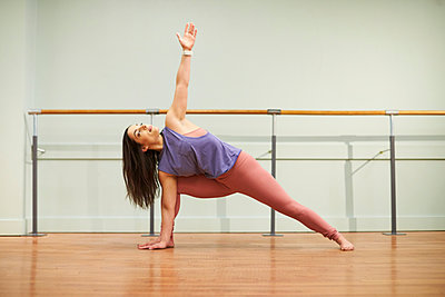 Woman doing yoga indoors - p343m2046890 by Josh Campbell