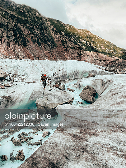 Two climber crossing melt-water river on glacier - p1166m2212336 by Cavan Images