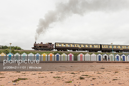 Steam train with bathing houses in the foreground - p1208m2111101 by Wisckow