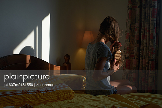 Woman sit on bed and comb her hair in the bedroom - p1607m2181550 by zhushman