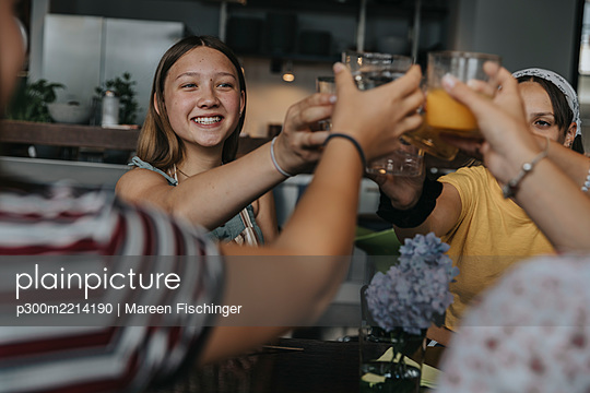 Group of teenage girls clinking glasses at homemade brunch - p300m2214190 by Mareen Fischinger