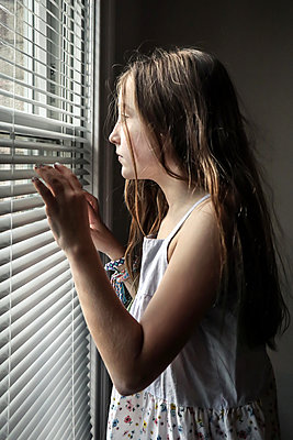 Girl looks through blinds at the window  - p1019m2134679 by Stephen Carroll