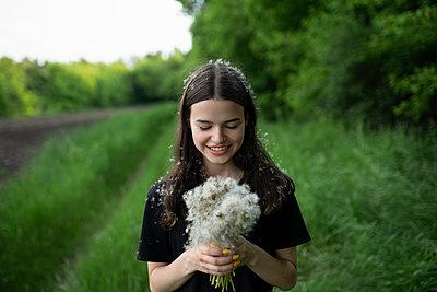 Smiling teenage girl holding dandelions in a field - p1427m2123597 by vyacheslav chistyakov