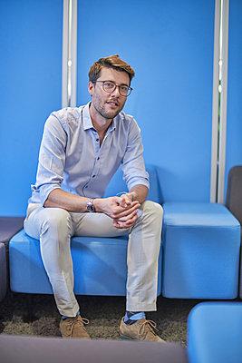 Portrait of businessman sitting on light blue stool in an office - p300m1587485 von Benjamin Egerland
