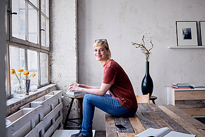 Portrait of smiling woman with coffee mug sitting on desk in loft - p300m2030182 by Rainer Berg