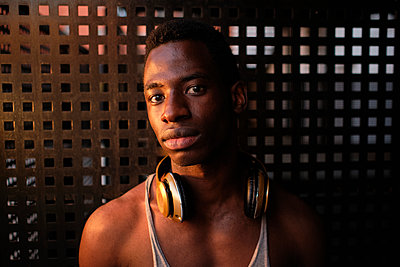 Young man with headphones around neck in front of metal wall at gym - p300m2273623 by Antonio Ovejero Diaz