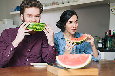 Portrait of happy young couple eating watermelon at kitchen table - p301m1029281f by Halfdark