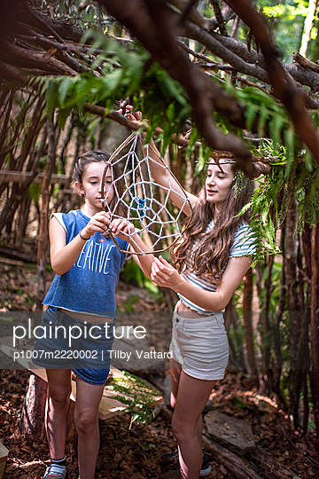 Two girls building a dreamcatcher - p1007m2220002 by Tilby Vattard