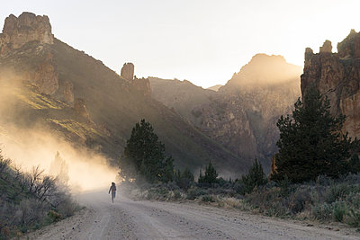 Rear view of female hiker running on dirt road against mountains - p1166m1485977 by Cavan Images