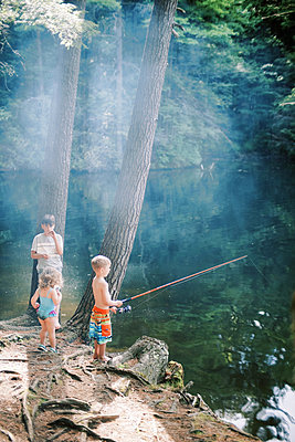 Three little friends fishing together at a lake in Connecticut - p1166m2193825 by Cavan Images
