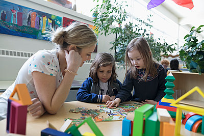Preschool teacher and girl students assembling jigsaw puzzle in classroom - p1192m1560174 by Hero Images