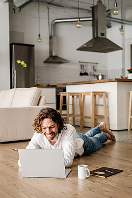 Smiling man lying on the floor at home using laptop - p300m2143959 by Giorgio Fochesato