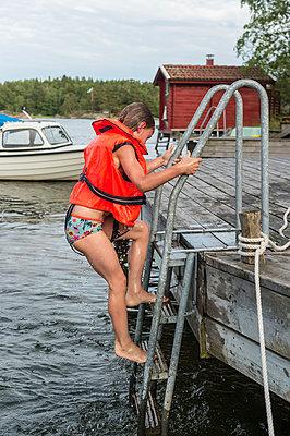 Girl climbing on jetty - p312m1025069f by Fredrik Schlyter