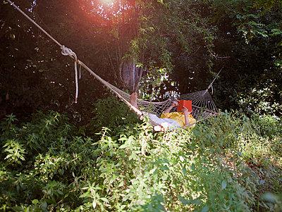 Man reading in hammock outdoors - p42917631f by Judith Wagner Fotografie