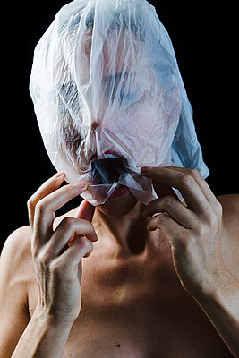 Woman with a translucent plastic bag on her head - p590m1508641 by Philippe Dureuil