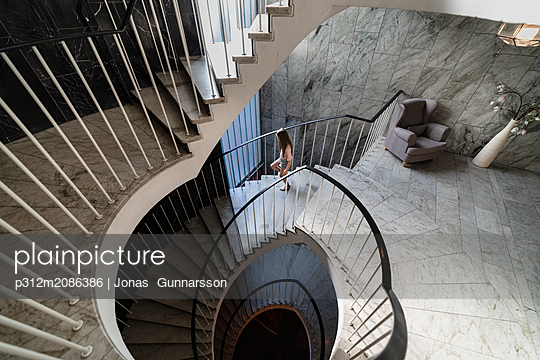 Girl walking down stairs - p312m2086386 by Jonas  Gunnarsson