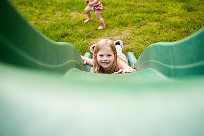 Portrait of happy girl sliding while brother playing in playground - p1166m1473769 by Cavan Images