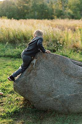 Four year old boy climbing a big boulder. - p1166m2151886 by Cavan Images
