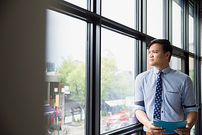 Pensive businessman looking out office window - p1192m1173851 by Hero Images