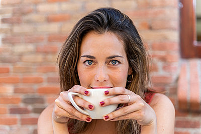 Portrait of young woman drinking cup of coffee - p300m2131666 by VITTA GALLERY
