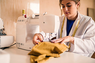 Young female tailor using sewing machine at workbench - p300m2293501 by LUPE RODRIGUEZ
