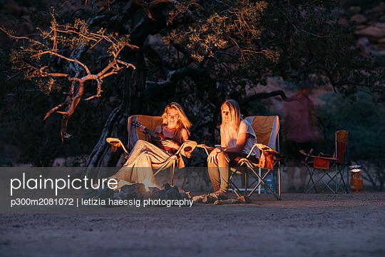 Namibia, friends sitting at campfire playing guitar - p300m2081072 by letizia haessig photography
