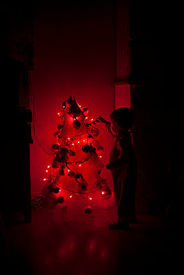 Little boy in pyjamas decorating handmade Christmas tree - p1028m1193409 by Jean Marmeisse