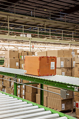 Conveyor belt system and cardboard boxes of products in a distribution warehouse. - p1100m2002287 by Mint Images