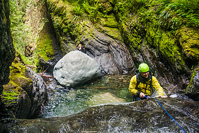 Man smiles while rappelling over the edge of a waterfall. - p1166m2138004 by Cavan Images