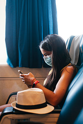 Mid adult woman wearing mask using mobile phone while sitting on seat in cruise ship - p300m2220805 by Ezequiel Giménez