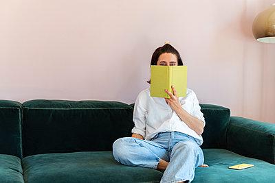 Frau versteckt sich hinter einem Buch - p432m2175456 von mia takahara
