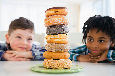 Boys admiring stack of donuts on counter - p555m1410975 by JGI/Jamie Grill