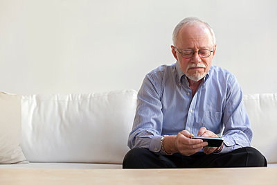 Caucasian man using tablet computer on sofa - p555m1464275 by Peter Dressel