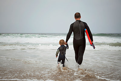 Caucasian father and son preparing to surf together - p555m1479235 by Pacific Images