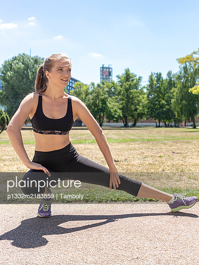 Young woman doing stretching exercise in a park  - p1332m2183859 by Tamboly
