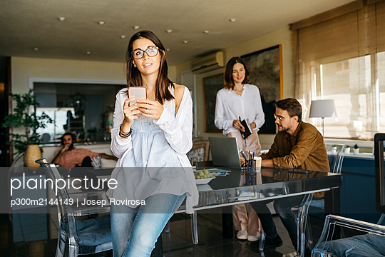 Portrait of woman with cell phone and friends working in background at home - p300m2144149 by Josep Rovirosa