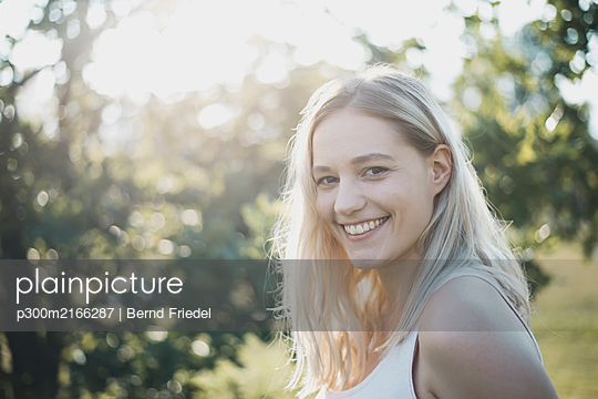 Portrait of blond young woman in nature - p300m2166287 von Bernd Friedel