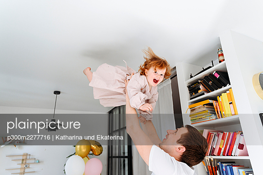 Father lifting playful daughter at home - p300m2277716 by Katharina und Ekaterina