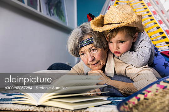 Senior woman reading book while boy lying on her at home - p300m2287284 by Stefanie Aumiller