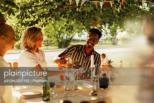 Happy friends having meal in garden - p312m2237152 by Plattform