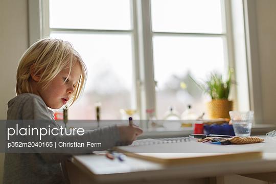 plainpicture - plainpicture p352m2040165 - Boy drawing at a table insi... - plainpicture/Folio Images/Christian Ferm