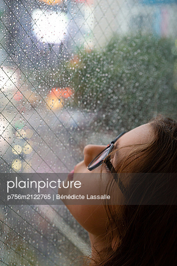 Girl looks through window with raindrops - p756m2122765 by Bénédicte Lassalle