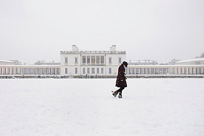 Woman walking in snowy landscape in Greenwich park with Queen's House behind - p1072m829404 by Neville Mountford-Hoare