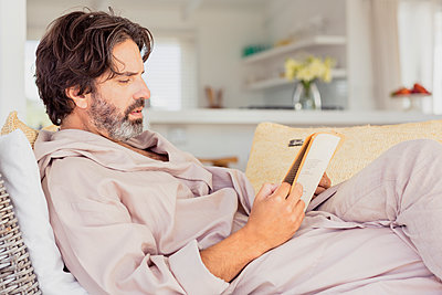 Relaxed man in bathrobe reading a book - p300m2167522 by Floco Images